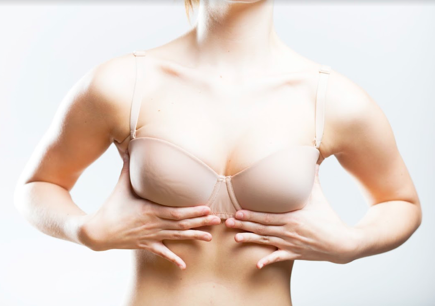 A woman using her hands to lift up the front of her bra