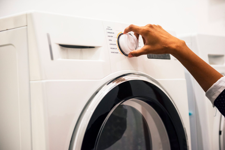 Woman's hand adjusting the dial on a washing machine